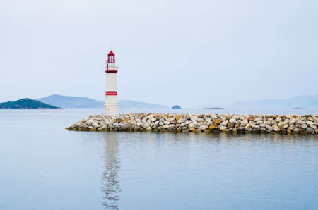 Lighthouse on a stone road in the middle of calm sea with views of mountains and fog.