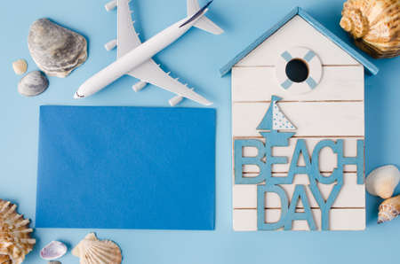 Empty blue paper with seashells and decorative airplane. Summer travel concept.