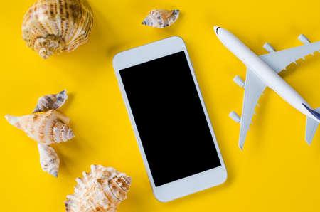 Empty screen smartphone, decorative airplane and seashells, template for app presentation.
