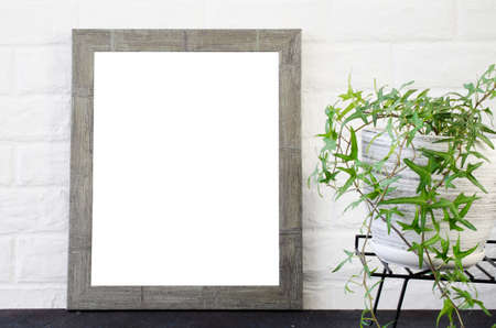 Poster or photo frame and beautiful plant in concrete pot. Scandinavian style room interior. Blank Mock up. Copy space.