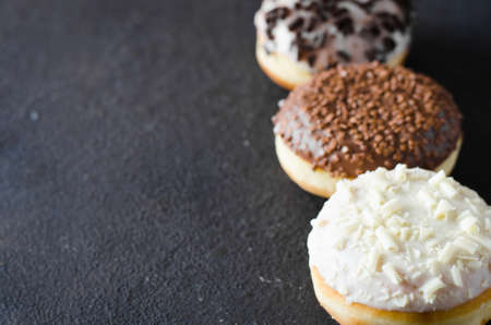Traditional donut day. Assorted donuts with chocolate glazed on concrete background. Top view