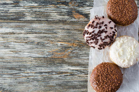 Traditional donut day. Assorted donuts with chocolate glazed on wooden background. Top view 写真素材
