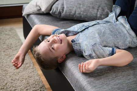 Cute funny boy lying upside down on sofa looking at camera, smiling playful child boy having fun at home on couch. 写真素材