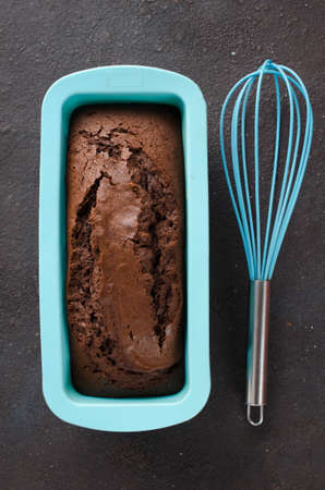 Freshly baked homemade chocolate bread or cake on dark background, rustic style. Top view.