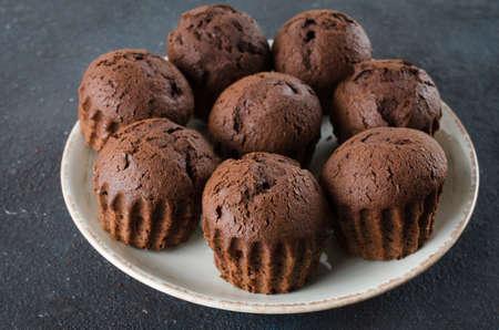 Plate full of chocolate muffins on dark background. Delicious chocolate dessert. 写真素材