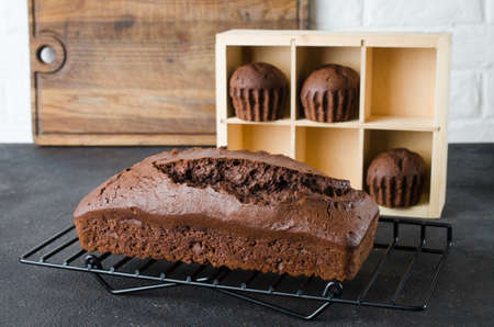 Freshly baked homemade chocolate bread or cake and chocolate muffins on dark background, rustic style. Selective focus.