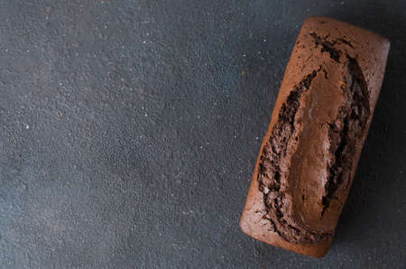 Freshly baked homemade chocolate bread or cake on dark background, rustic style. Selective focus, space for text. 写真素材