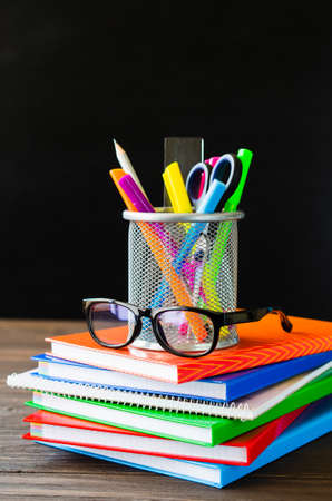 Back to school. Stack of books, school supplies and glasses on black board background. Education concept.