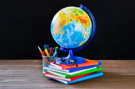 Back to school. Stack of books, school supplies, globe and glasses on black board background.