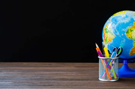 Back to school. School supplies and globe on black board background. Education concept.