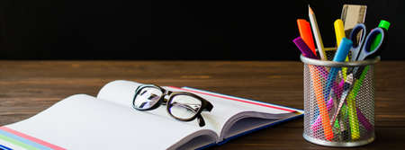 Back to school. Open empty notebook with glasses and school stationery on black board background. Education concept.