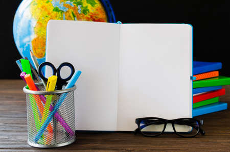 Back to school. Education concept with open empty notebook and school supplies.