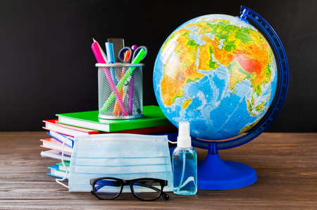 Back to school during quarantine. Education concept. School supplies with medical mask and sanitizer. 写真素材