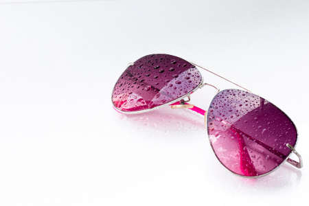droppings: pink sunglasses and drops on an isolated white background Stock Photo