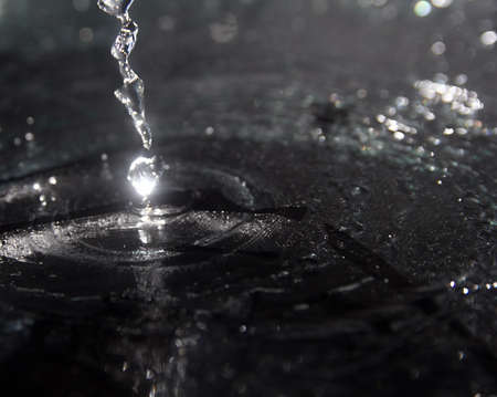 brit: squirt, splash of water on a black background, drops Stock Photo