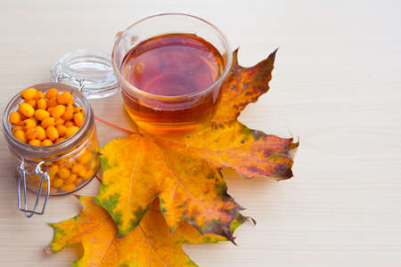 sea-buckthorn berries and autumn leaves, alternative medicine, treatment in the fall Stock Photo