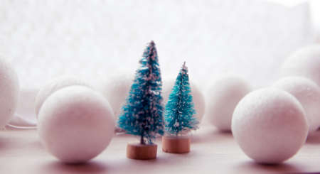 next year: two small green toy Christmas tree on a wooden background as a symbol of the new year with place for text, next to white Christmas
