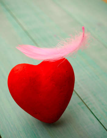 red heart one closeup, it is a pink feather, the concept of love, Valentines day, wedding, blue background Stock Photo