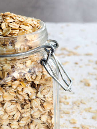 wood texture: Rolled in a glass jar, spilled cereal, the concept of healthy food, space for text Stock Photo