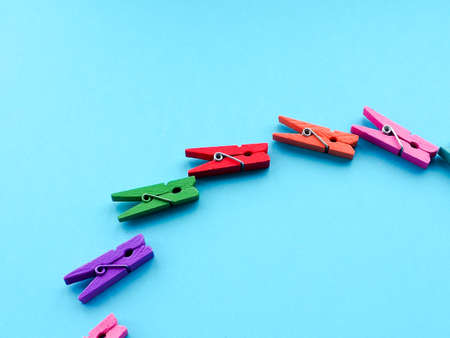 many colored clothespins on a blue background, as a substrate, pin clothes peg