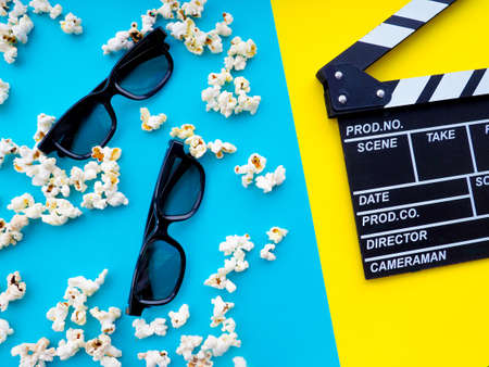 Popcorn, glasses for cinema and clapperboard on colorful background.