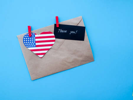 advertise with us: envelope, USA flag hanging on colorful pegs clothespin on a line against blue background. United States of America, Thank you, independence day