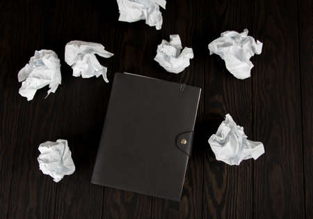 White note pad on a wooden table. Writing concept - crumpled up paper wads with Notepad