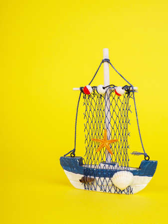 Vintage sailing boat ship on yellow. Wooden marine miniature, handmade souvenirs, minimalism is the concept of vacation. Stock Photo