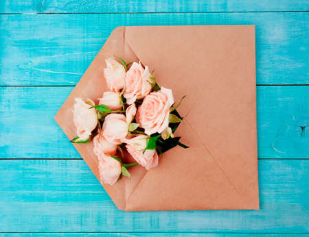 Envelop with white card and rose background. Top view., Envelope with flowers summer, spring