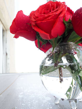 a bouquet of bright red roses in a glass vase