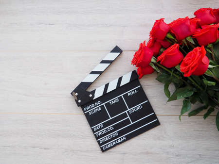 vintage classic clapperboard on brown wooden table whis red roses.