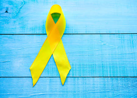 Childhood Cancer Day. Yellow Ribbon on blue background.