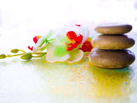 Spa pink orchid with massage stones on blue wooden background.