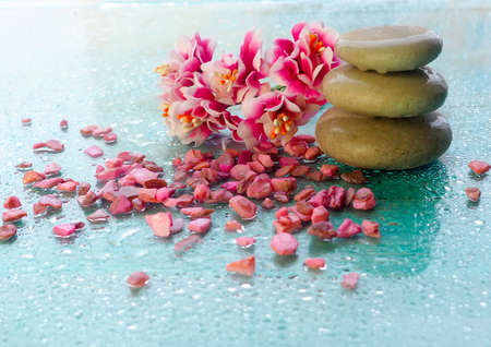 Spa pink orchid with massage stones on blue wooden background Imagens