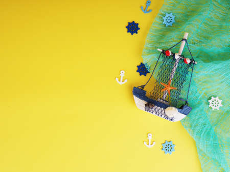 Vintage sailing boat ship on yellow. Wooden marine miniature, handmade souvenirs, realistic models, the concept of home away from home 免版税图像