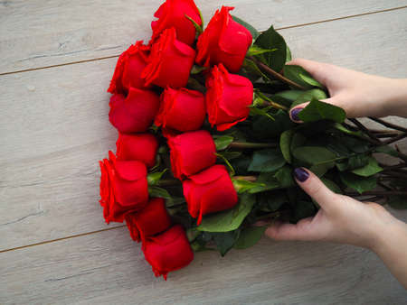 Preparing a gift, on a wooden table, with roses. Female hand holding a gift, wrapped with ribbon, on a background of red roses, the space under the text Stock Photo