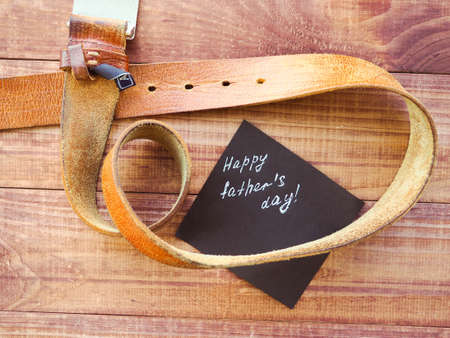 Happy Fathers Day the leather strap on wooden background. Greetings and presents Stockfoto