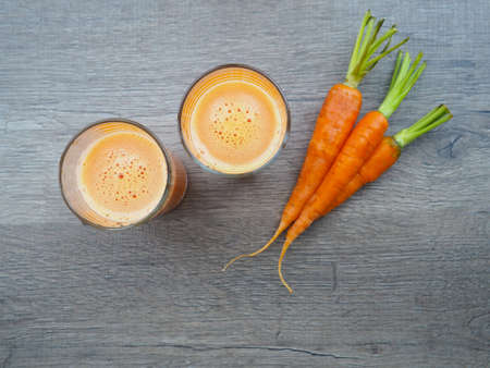 glass of fresh carrot juice with vegetables on wood background. high shot