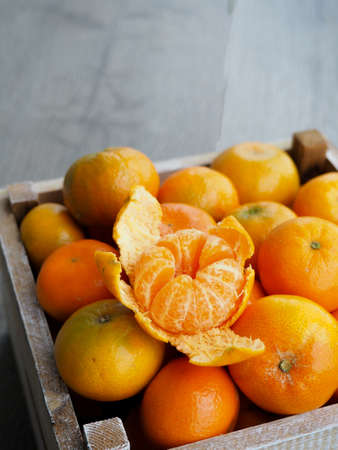 Fresh tangerines in an old box . On wooden background. Free space for text . Stockfoto