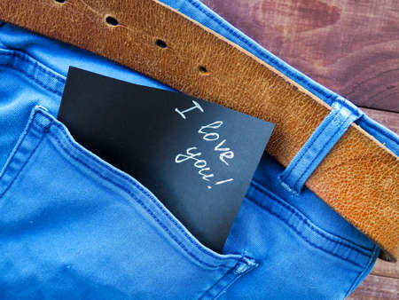 the phrase, a note I love you in the jeans pocket, on a wooden background, space for text 免版税图像