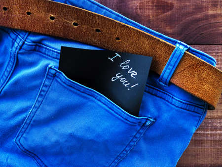 the phrase, a note I love you in the jeans pocket, on a wooden background, space for text Stockfoto