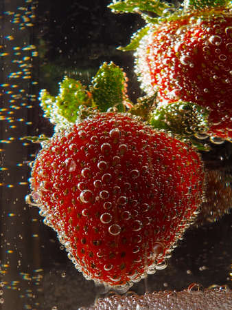 Strawberry in a water on black background, Strawberry in a water on black background, classy, commercial, cover, closeup, selective focus Stockfoto