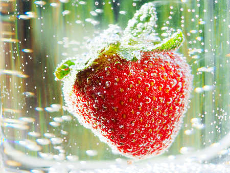 Strawberry in a water on color background, Strawberry in a water on black background, classy, commercial, cover, closeup, selective focus