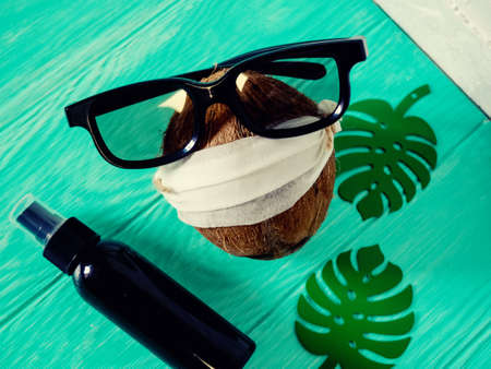 coconut in a homemade mask to sit at home in the country close. Near antiseptic. Coronavirus outbreak or Covid-19, Concept of Covid-19 quarantine. Dangerous COVID virus, Doomsday panic people panic. Stock Photo