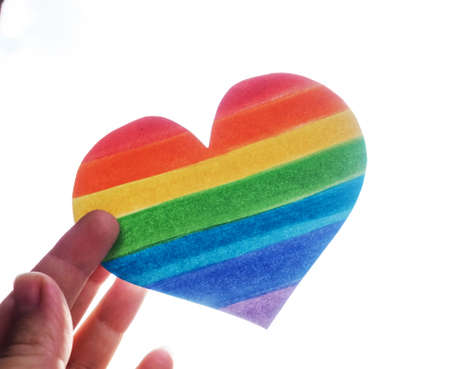 Rainbow Heart, lgbt rights concept, hand holds a heart painted like a LGBT flag, silhouetted against sun.