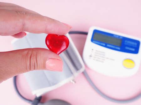 Stethoscope, heart shape, blood pressure monitor. female hand holding the heart, blood pressure. Imagens