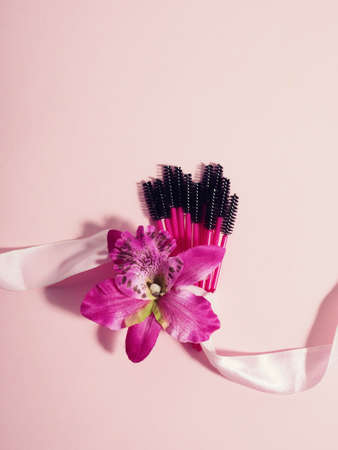 Bouquet of eyelash brushes, tied with a ribbon on a pink background.