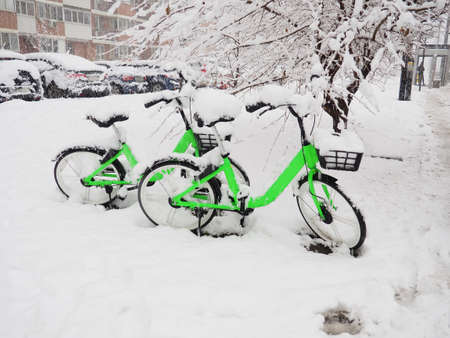 Two green bikes for hire under the snow, snow apocalypse.