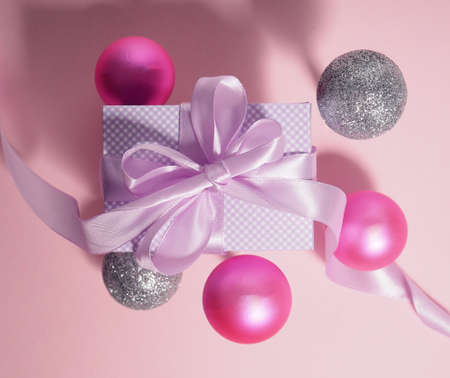 Gift box with purple ribbon surrounded by pink balloons. 版權商用圖片