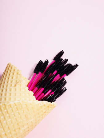Creative, eyelash brushes in ice cream cones on pink background, eyelash extensions.